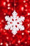 Un juguete del copo de nieve en fondo rojo del bokeh Imagen de archivo