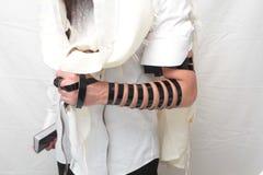 Un juif orthodoxe religieux avec le bras-tefillin sur sa main gauche prie A l'homme que juif prépare le tefillin Image stock