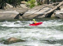 Un kayaker tire les rapids/ photos stock