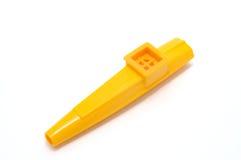 Un Kazoo amarillo hecho del plástico aislado en el fondo blanco. Fotografía de archivo