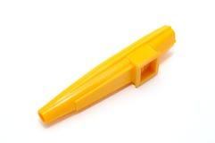 Un kazoo giallo fatto di plastica isolata su fondo bianco. Immagini Stock Libere da Diritti