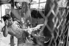 Un kickboxer pratiquant ses éruptions de jambe contre un sac de poinçon tiré par une barrière de maillon de chaîne et en noir et  photo libre de droits