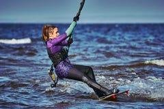 Un kiter femenino resbala en la superficie del agua Salpica de mosca del agua aparte foto de archivo libre de regalías