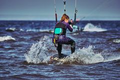 Un kiter femenino resbala en la superficie del agua Salpica de mosca del agua aparte fotografía de archivo
