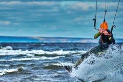 Un kiter masculin glisse sur la surface de l'eau Éclabousse de la mouche de l'eau à part images libres de droits
