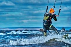 Un kiter masculin glisse sur la surface de l'eau Éclabousse de la mouche de l'eau à part photos stock
