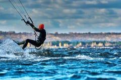 Un kiter masculin glisse sur la surface de l'eau Éclabousse de la mouche de l'eau à part image stock