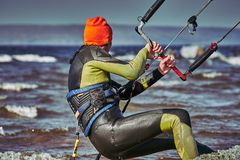 Un kiter masculino resbala en la superficie del agua Salpica de mosca del agua aparte imágenes de archivo libres de regalías