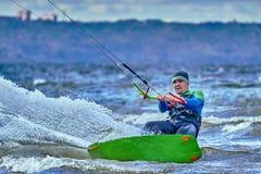 Un kiter masculino resbala en la superficie del agua Salpica de mosca del agua aparte fotografía de archivo