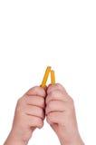 Un lápiz de terminal de componente quebrado en las manos de un niño Imagen de archivo libre de regalías