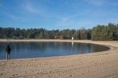 Un lac congelé de natation avec une petite plage Image stock