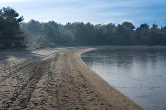 Un lac congelé de natation avec une petite plage Images stock