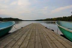 un lac lisse, pilier, bateau Photos stock