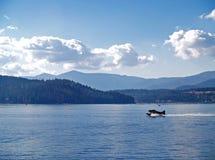 Un lac mountain avec un avion d'eau Photos stock