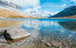 Un lac transparent de montagne avec une roche Image stock