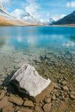 Un lac transparent de montagne avec une roche Photos stock