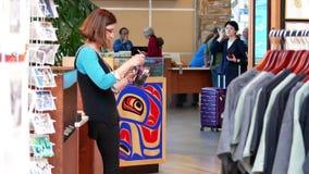 Un lado de pluma de la media del trabajador de la tienda de regalos en el aeropuerto de YVR