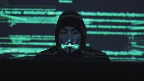 Un ladrón de sexo masculino en trabajos de una máscara sobre un ordenador en un cuarto oscuro el código de ordenador se refleja e almacen de metraje de vídeo