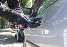 Un ladrón está intentando escoger la cerradura de un coche imagen de archivo libre de regalías