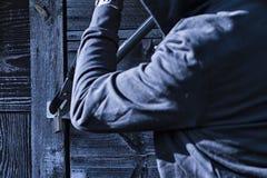 Un ladrón rompe una cerradura con un cortador de perno Imagen de archivo libre de regalías