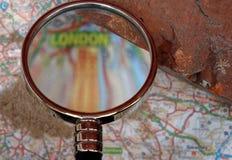 Un ladrillo viejo de la casa sobre un mapa borroso de Londres foto de archivo libre de regalías