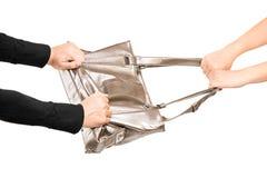 Un ladro che prova a rubare una borsa da una ragazza Immagine Stock