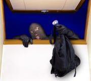 Un ladro entra nella casa Immagini Stock