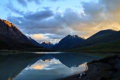 Un lago ad alta altitudine calmo Ak-Oyuk al tramonto Fotografia Stock