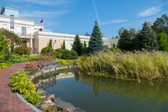Un lago artificial sobrepuesto con de piedra y plantado con los anfitriones y las flores por los desperdicios cerca de la casa foto de archivo libre de regalías