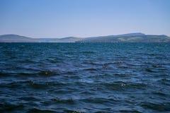 Un lago azul contra el contexto de las montañas y de una regata del yate en la distancia Foto de archivo