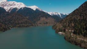 Un lago azul está situado entre las montañas y los árboles altamente coronados de nieve almacen de metraje de vídeo