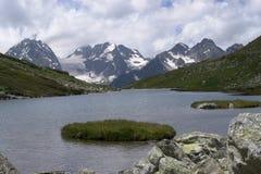 Un lago calmo magnifico dell'alta montagna con le rive verdi Immagine Stock