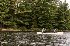 Un lago canada Ontario di due coppie dei fiumi su una canoa Canoes sul parco nazionale del Algonquin dell'acqua immagini stock