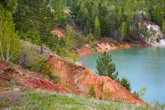 Un lago con los bancos de la arcilla coloreada Imagen de archivo