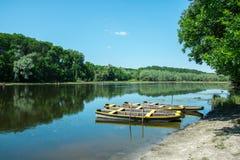 Un lago con los barcos de madera por la costa imagenes de archivo