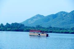 Un lago con un barco de casa Foto de archivo