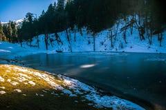 Un lago congelado encima de una montaña foto de archivo