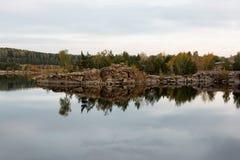 Un lago de piedra del otoño con el abedul y el pino Imagen de archivo libre de regalías
