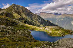 Un lago della montagna in un periodo del sole Fotografia Stock