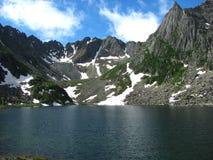 Un lago enorme rodeado por los picos nevosos foto de archivo libre de regalías
