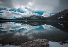 Un lago freddo vicino a Canmore Alberta con una riflessione perfetta fotografia stock libera da diritti