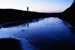 Un lago ghiacciato con la siluetta dell'uomo Immagini Stock
