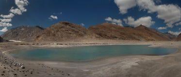 Un lago glacial hermoso con una superficie de la turquesa del agua clara en el medio de la moraine rodeada por las altas montañas Imagenes de archivo