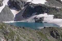 Un lago magnifico della montagna circondato dai pendii rocciosi ripidi Immagine Stock Libera da Diritti