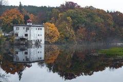 Un lago refleja el follaje de otoño en una mañana brumosa imagenes de archivo