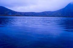Un lago sotto una cresta della montagna immagine stock