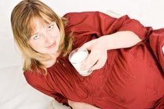 Un lait de consommation enceinte de dame photographie stock libre de droits