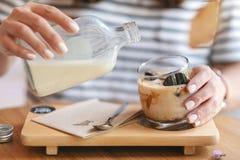 Un lait se renversant de femme dans un verre de caf? de gla?on en caf? photographie stock libre de droits