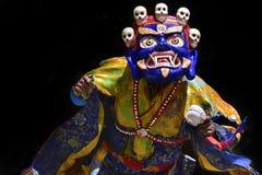 Un lama budista en un traje tibetano ritual y una máscara de Mahakala azul realizan la danza sagrada del Cham Imagenes de archivo