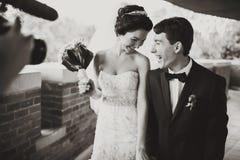 Un lanzamiento del cameraman un par sonriente de la boda Foto de archivo